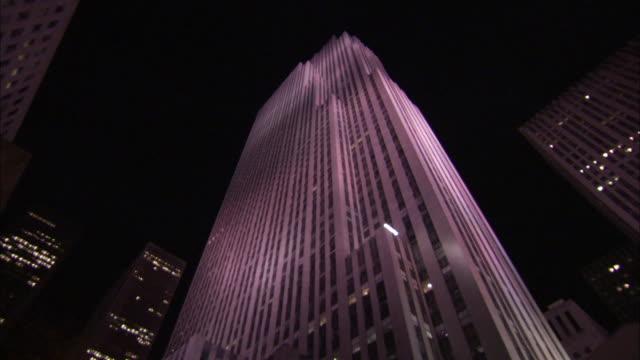 vídeos de stock, filmes e b-roll de pink floodlights illuminate the ge building at night. available in hd - centro rockefeller