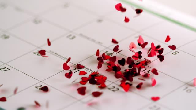 Pink heart confetti falling on calendar