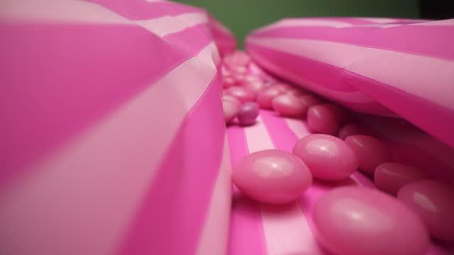 vídeos de stock e filmes b-roll de pink jellybeans on striped wrapping paper - coinfeitos