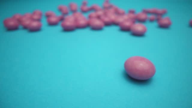 ターコイズの背景にピンクのゼリービーンズ - ジェリービーンズ点の映像素材/bロール