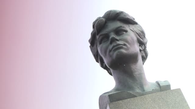 Pink light glows behind the Valentina Tereshkova statue. Available in HD.