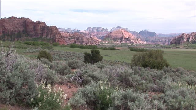 pink light illuminates a rugged mountain surrounded by grasslands. - extreme terrain stock videos & royalty-free footage