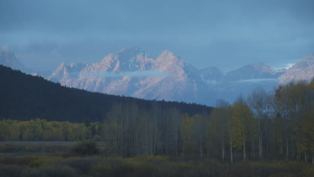 pink mountains glow under a purple sky at oxbow bend in grand teton national park. - grand teton national park stock videos & royalty-free footage