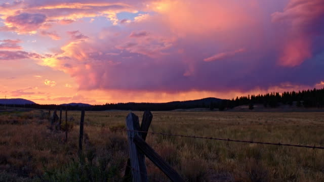 stockvideo's en b-roll-footage met pink rain thunderstorm sunset and wooden barbed wire fence in the desert - ranch