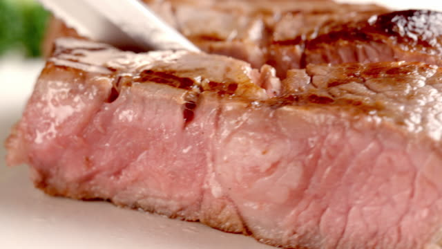 vídeos de stock e filmes b-roll de ecu pink rare slice of meat pivoted away from sirloin steak to show degree of cooking between rare and medium rare  - fatia