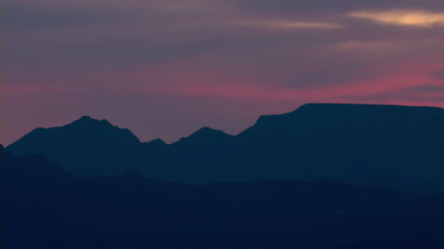 A pink sky silhouettes desert mountains in Arizona.