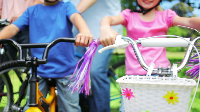 Bike handlebar tassels blowing in the wind before the camera rises to show a family sitting on bikes