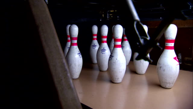pins standing at end of lane, blue ball moving toward pins, knocking over all but 2 pins, automatic pinsetter clearing & resetting pins. sport,... - bowling ball stock videos & royalty-free footage