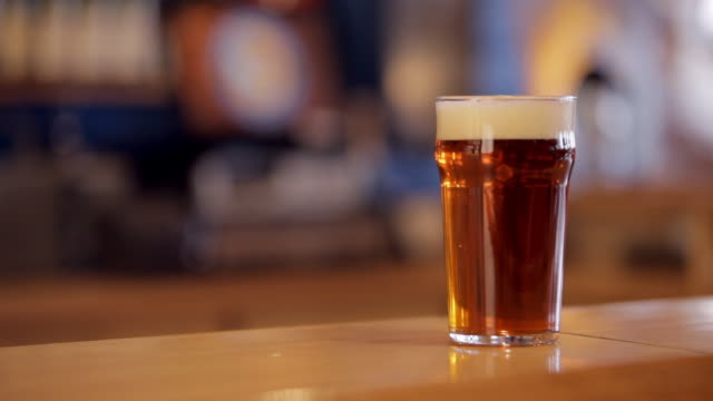 pint of amber beer on a bar - pint glass stock videos & royalty-free footage