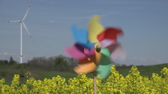 zo pinwheel at wind turbine in rape field - girandola video stock e b–roll