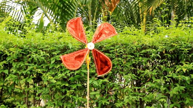 tappezzi mulino a vento o di mulini a vento contro il vento e filatura in giardino - bandierina da golf video stock e b–roll