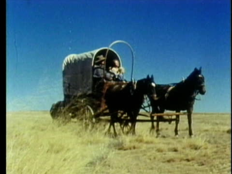 vidéos et rushes de 1959 reenactment ws pan pioneer family in covered wagon on the midwest plains - ouest américain