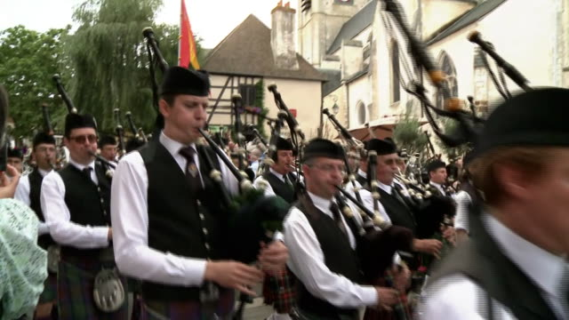 pipe band marching through aubignysurnere in celebration of the auld alliance - bagpipes stock videos & royalty-free footage