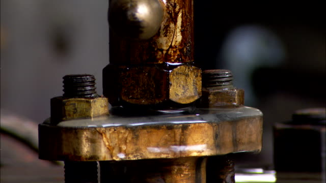a pipe leaks around a spindle on a tank in a water pumping station. - leaking stock videos & royalty-free footage