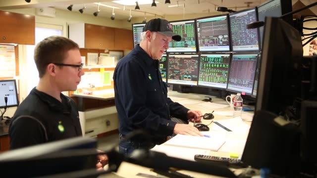 A pipeline controller and a wells optimization engineer in the control room at the BP Plc Eastern Offtake Center in Prudhoe Bay as well as control...