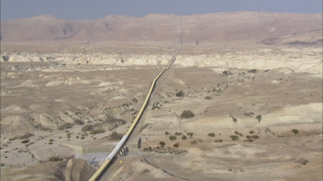 aerial pipeline crossing judea desert, israel - terreno accidentato video stock e b–roll