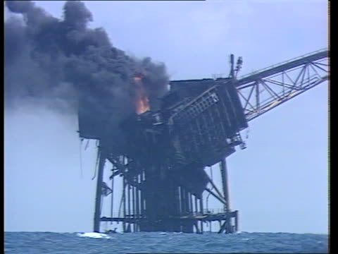 recovery work continues; north sea: ext lms piper alpha oil rig as smoke rises from upper structure and wreckkage in sea next to it zoom... - alpha cell stock videos & royalty-free footage