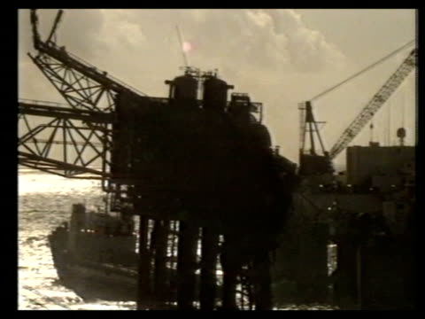 c cranes and salvage boat by wreckage airv wreckage in silhouette day airv stern of salvage boat rocking up and down in rough sea airv lifting barge - rough stock videos & royalty-free footage