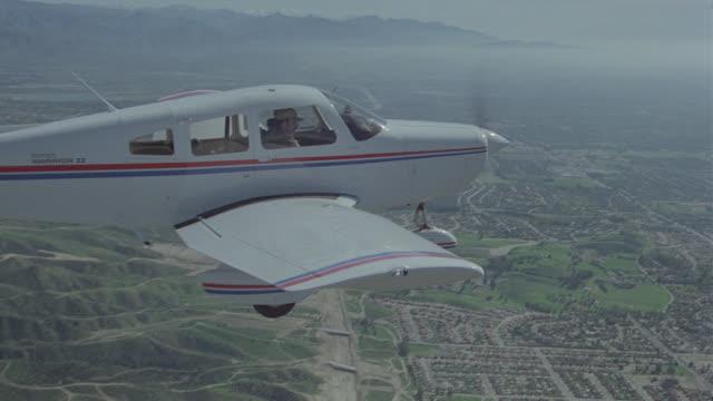a-a piper cherokee over mountains - プロペラ機点の映像素材/bロール