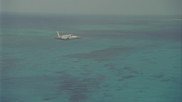a-a piper navajo twin over ocean - プロペラ機点の映像素材/bロール