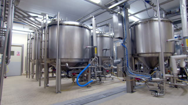 pipes and tanks in a food factory - rostfreier stahl stock-videos und b-roll-filmmaterial