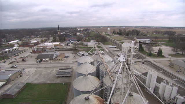 stockvideo's en b-roll-footage met pipes, silos, and large tanks surround a factory in a small town. - silo