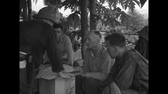 vidéos et rushes de pipesmoking us gen hanford macnider examines a map with other men / army doctors scrub up outside while wearing surgical masks leaving the operating... - guerre du pacifique