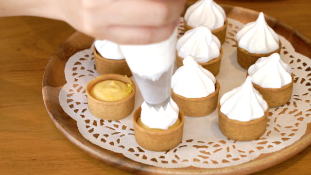 CU Piping meringue onto lemon tartlets