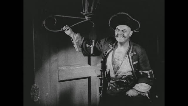 a pirate is ordered to cut a victim's stomach to remove a swallowed ring - seeräuber stock-videos und b-roll-filmmaterial