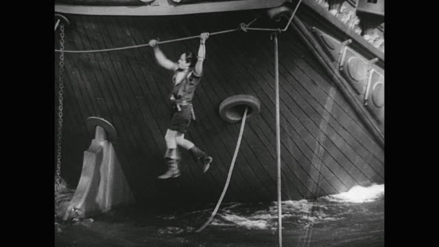 pirate (douglas fairbanks) jams a large ship's rudder and climbs on board the luxurious craft - rope stock videos & royalty-free footage