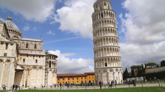 Pisa, tourists walking in front of the leaning tower and the cathedral