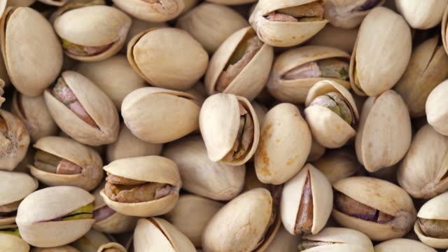 vídeos de stock e filmes b-roll de pistachio nuts 4k turntable loop - top down - fruto seco
