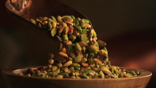 pistachios falling into a bowl