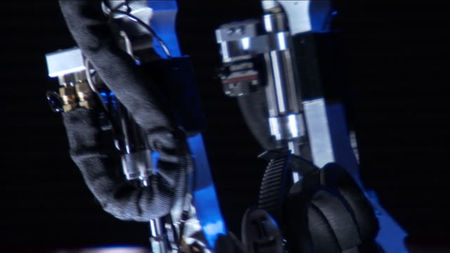 pistons and actuators shape the legs of a futuristic exoskeleton suit. - exoskeleton stock videos & royalty-free footage