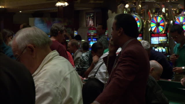 a pit boss talks on the phone while watching over a craps table. - craps stock videos & royalty-free footage