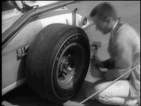 b/w 1965 pit crew man hammering tire on race car on phoenix international raceway / newsreel - 試運転点の映像素材/bロール