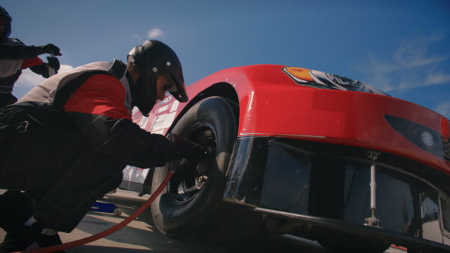 SLO MO. Pit crew mechanic removes lug nuts to change tire on stock car on race day.