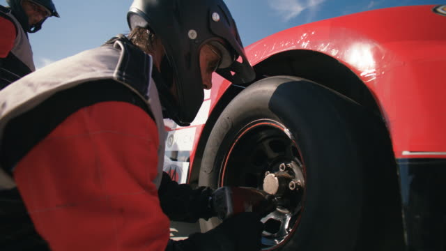 Stock car pit-crewman tightens new race-car tire lug-nuts