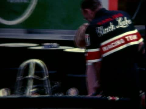 "vídeos de stock, filmes e b-roll de pit crew member holding chalkboard: ""hobbs, 85 /"" pit crew pushing carling indy race car 73 driven by david hobbs from pit / crew fueling 73, then... - 1973"