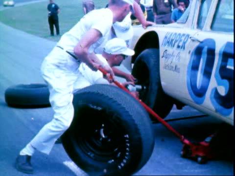 pit crew members changing tires of stock cars including 1962 pontiac during pit stops / crowd walking along infield passing display cars such as ford... - tyre stock videos & royalty-free footage