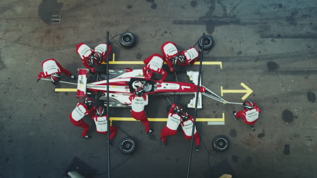 Pit crew members repairing Formula One car