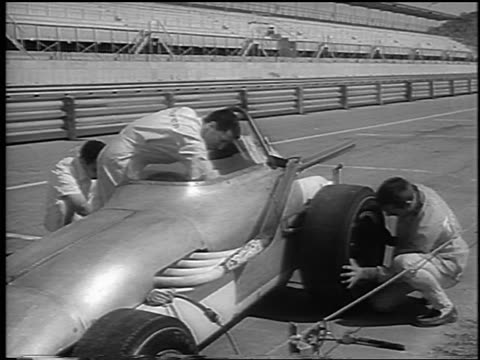 B/W 1965 pit crew preparing race car on test track before Indianapolis 500 / newsreel