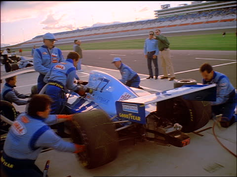 Pit crew quickly changing wheels on blue race car / zoom in crew member fastening wheel
