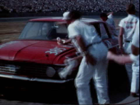stockvideo's en b-roll-footage met pit crew refueling ford stock car 0 gas spurting out rear end when filled / bald racing tire in pit / pit 3 sign / pit crew working on red stock car... - 1964
