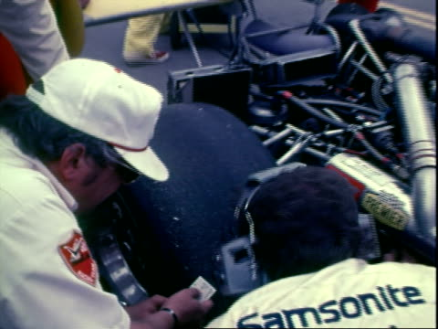 pit crew strapping buckling professional race car driver al unser sr into formula 1 race car indianapolis 500 / cu al unser sr wearing racing helmet... - seat belt stock videos & royalty-free footage