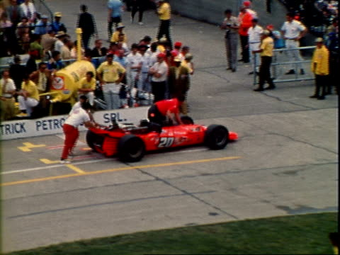pit crews working on Indy race cars including Jim McElreath Coyote Foyt in pit alley of Indianapolis Motor Speedway / pit crew pushing Jim McElreath...