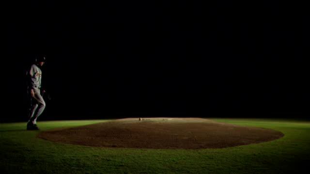 A pitcher picks up a baseball on a pitcher's mound.