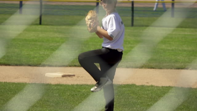 a pitcher pitches in a little league baseball game. - slow motion - basebollpitcher bildbanksvideor och videomaterial från bakom kulisserna