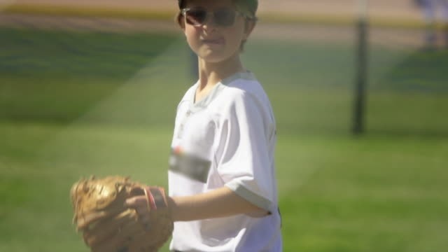 stockvideo's en b-roll-footage met a pitcher pitches in a little league baseball game. - slow motion - honkbal teamsport