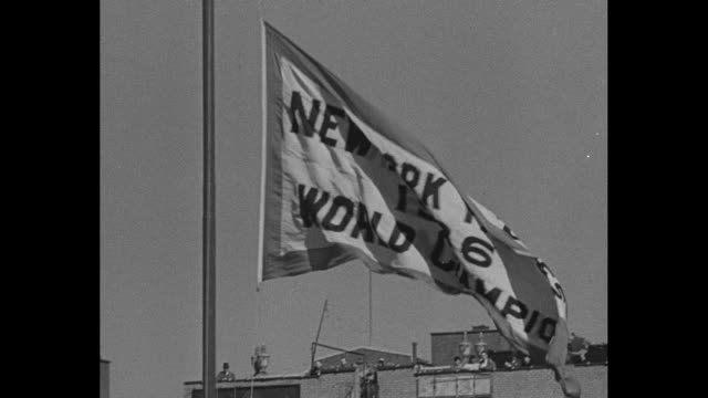 'BASEBALL SEASON OPENS pitcher throws at camera PLAY BALL' / Flag in light breeze 'New York Yankees 1936 World Series' / infield grandstands...